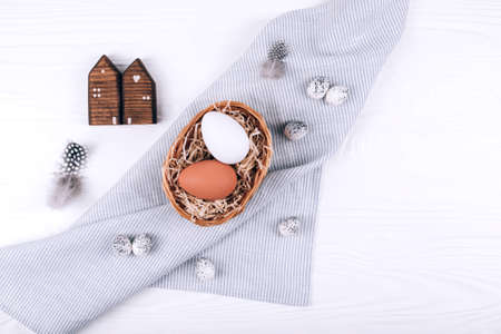 Easter eggs in the nest on textile napkin on white wooden background.