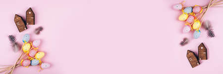 Banner made from colorful Easter eggs over pink background. Top view with copy space Imagens