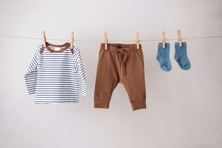 Baby clothes hanging on the rope on gray background.