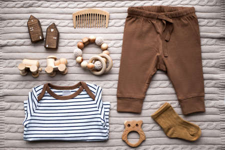 Baby clothing and accessories on beige background. Flat lay style.