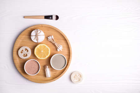 Cosmetic clay facial masks, sea salt, lemon and brush on white wooden background.