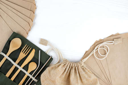 Eco bag with bamboo cutlery and paper envelopes on white background. Sustainable lifestyle. Zero waste and plastic free concept.