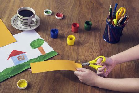 Boy cutting cardboard shape in class Stock Photo