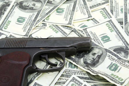 counterfeit: The pistol lies on a counterfeit money. Stock Photo