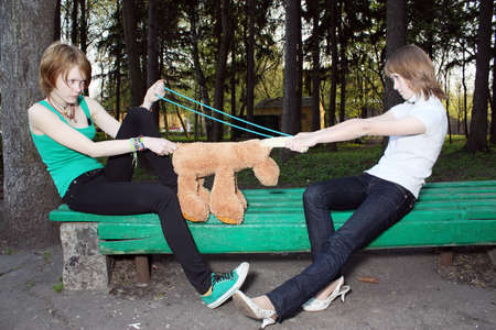 Two girls are fighting for a soft toy and a beads.  photo
