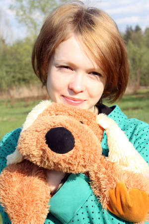 Portrait of the girl with a soft toy against spring wood and a green grass. Stock Photo - 4977837