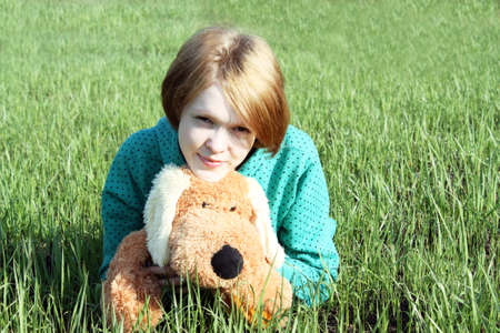 Portrait of the girl with a soft toy against a green grass. photo