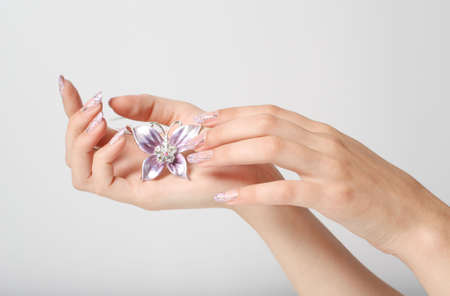 Female hands with beautiful manicure hold costume jewellery photo