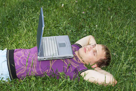Young guy lying down on the grass with laptop photo