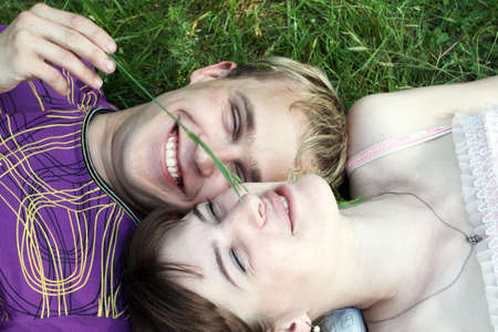 The young loving couple lies on a grass and laughs photo