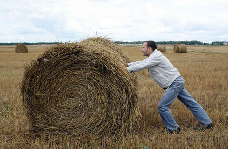 The man rolls a straw bale across the field photo