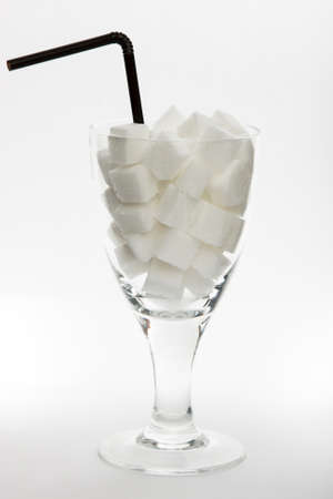 Sugar cubes in glass on bright background photo