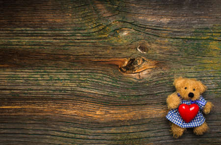 Teddy bear holding red heart on wooden background. Free space for your text. photo