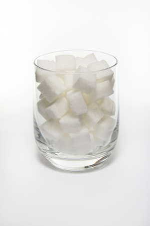 Sugar cube in glass on white background photo