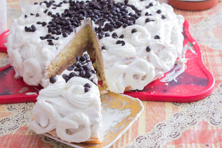 White cake decorated with cream and black chocolate