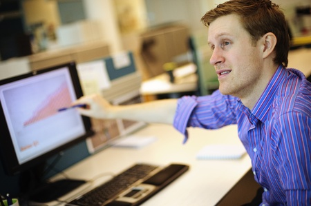 office use: Young businessman pointing at graph on PC  Stock Photo