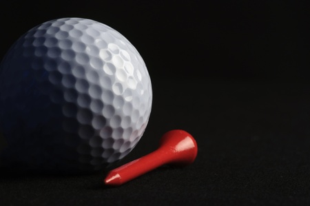 Golf ball with red tee on black background  Stock Photo