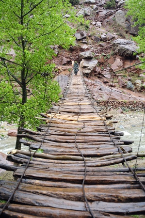 Simple suspension bridge with berber in the Ourika Valley in Morocko
