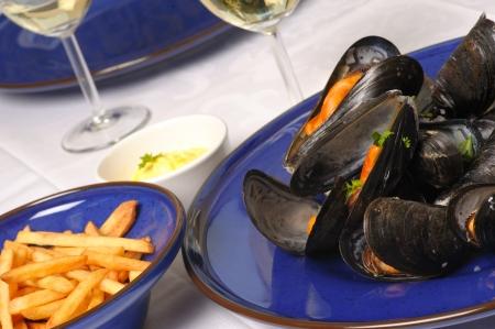 Gestoomde mosselen met wijn op blauw bord met frieten en mayonaise en glazen witte wijn