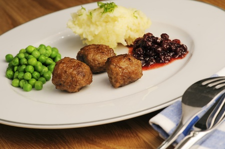 Traditional Swedish meatballs, served with peas, lingonberries and mashed potatoes  Stock Photo