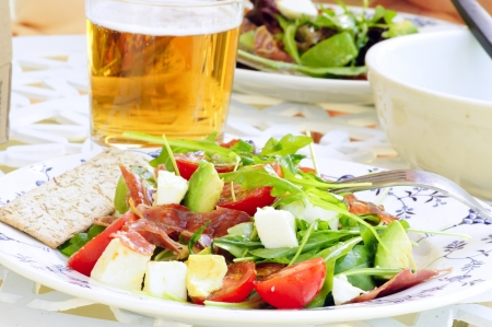 Beer and summer salad with fried dry-cured ham, avocado, mozzarella, rocket and tomatoes