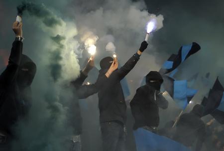 Voetbalfans in rook met vuurwerk