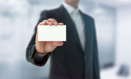 Business man holding name card isolated over white background. You can put your message on the card Archivio Fotografico