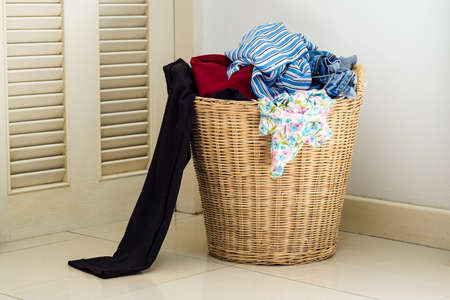 dirty clothes: Pile of dirty clothes in a washing basket Stock Photo