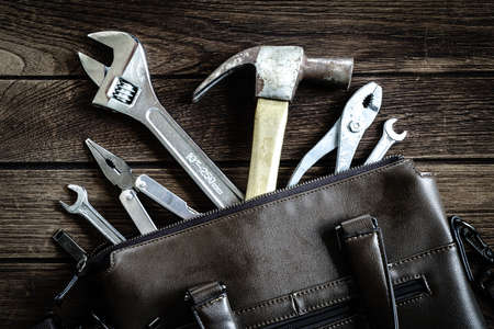 tools in leather bag - labor day and business fight background concept
