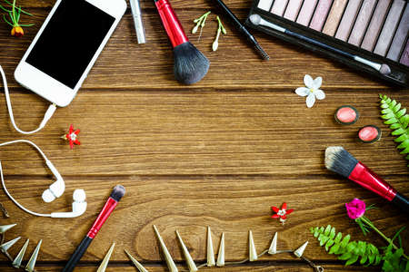 Top view of cosmetics and female accessories on wooden background