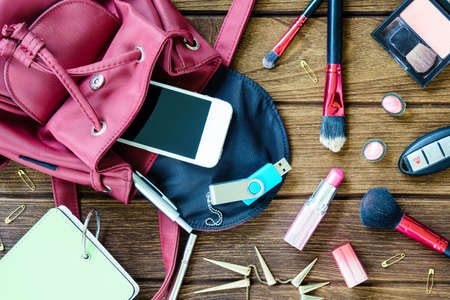 Top view of women bag stuff on wooden texture background Stock Photo