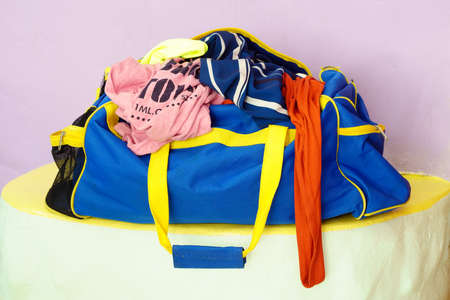 overfilled: crumpled clothes in travel bag Stock Photo