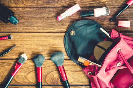Vista superior de los accesorios cosméticos bolsa de las mujeres cosas femeninas en el fondo de la textura de madera Foto de archivo