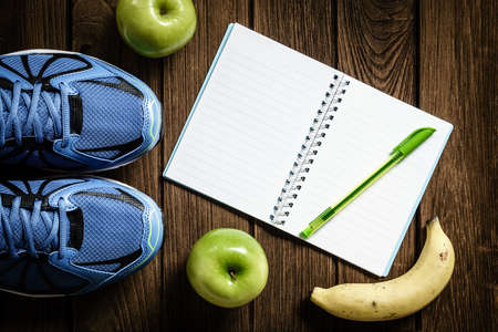 Sport shoes, apples and bananas  on a  wooden background. Sport equipment, healthy and active lifestyles, copy space for text. Conceptual photo. Top view Standard-Bild