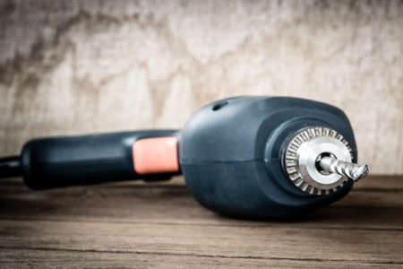 power drill closeup on wooden background