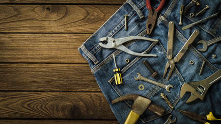 Construction tools and jeans on wooden background