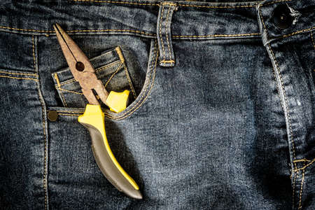 long nose: long nose pliers in jeans pocket concept and background for labor days