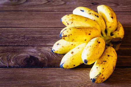 energizing: Bunch of fresh yellow bananas on a wooden background with copy space Stock Photo