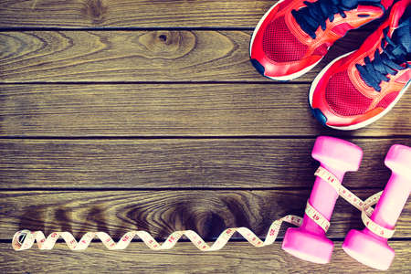 footware: Fitness, healthy and active lifestyles Concept, dumbbells, tape masure, sport shoes on wood background. copy space for text. Top view