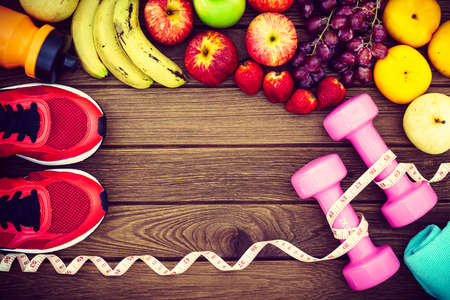 Fitness, healthy and active lifestyles Concept, dumbbells, sport shoes, bottle of waters, bananas,  and apples on wood background. copy space for text. Top view