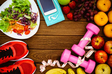 Fitness, healthy fruits, Fresh healthy salad, diet and active lifestyles Concept, dumbbells, Fresh healthy salad, fresh fruits, sport shoes, smart phone on wood background. copy space for text. Top view Zdjęcie Seryjne