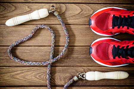 Fitness love concept - Top view of sport shoes and jump rope in heart shape on wooden  background