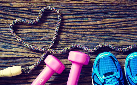 Fitness workout love concept - Top view of sport shoes, dumbbells and jump rope in heart shape on wooden background Standard-Bild