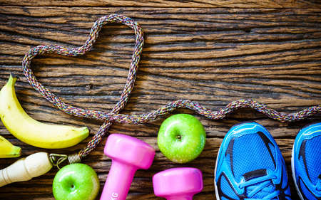 Fitness workout love and healthy fruit eating concept - Top view of bananas, green apples, sport shoes, dumbbells and jump rope in heart shape on wooden background Standard-Bild