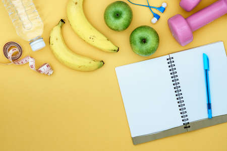 Still Life - Fitness, healthy and active lifestyles Concept, dumbbells, notebook, measuring tape, Jump rope, bananas, apples, bottle of water, and headphone. Top view with copy space for text.
