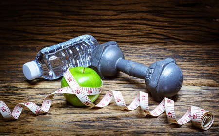 Fitness, healthy eating and active lifestyles Concept, dumbbells,  apples and bottle of water