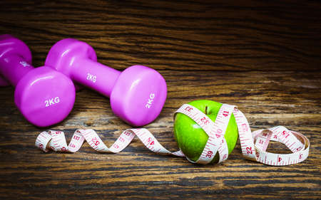 Fitness, healthy eating and dieting concept, dumbbells,  apples and measuring tape