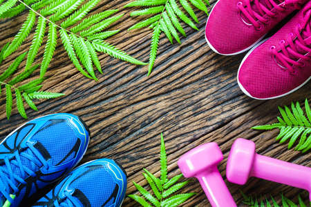 healthy sport: Fitness, healthy and active lifestyles lover Concept, male and female sport shoes and pink dumbbells on wooden background. copy space for text. Top view