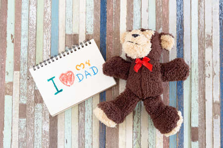 Fathers day greeting card concepts with I love my Dad text and monkey cute dolls. Top view on wooden background.