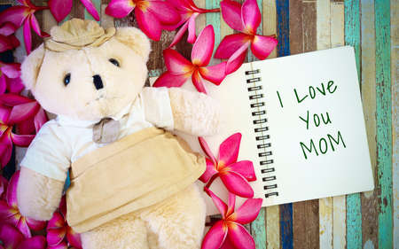 Mothers day greeting card concepts with I love you Mom text and cute Teddy bear doll. Top view on wooden background. Stock Photo